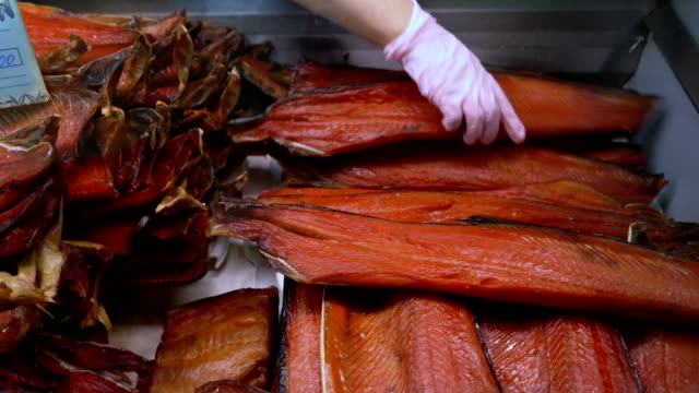 close-up hand showing smoked salted red salmon on counter at fish market - filetto video stock e b–roll