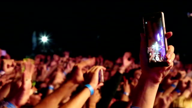 Bидео close-up - hand with a smartphone against the background of a crowd at concerts