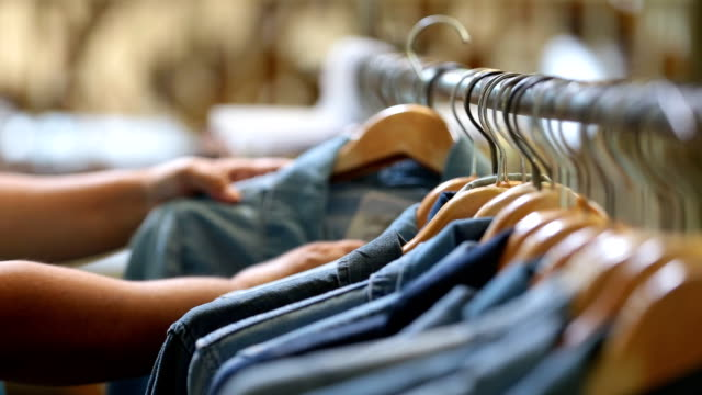Closeup hand woman in the shop looks through jackets and shirts, which are hanging on the racks Closeup hand woman in the shop looks through jackets and shirts, which are hanging on the racks coathanger stock videos & royalty-free footage