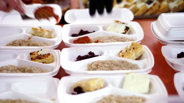 vídeos de stock e filmes b-roll de close-up, hands in disposable gloves pack charity hot meals in lunchboxes, to be free delivered to poor people by volunteers during lock down covid19 . food delivery - benefits