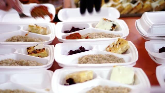 närbild, händer i engångshandskar pack välgörenhet varma måltider i matlådor, att vara fri levereras till fattiga människor av volontärer under låsa covid19 . leverans av livsmedel - välgörenhet bildbanksvideor och videomaterial från bakom kulisserna
