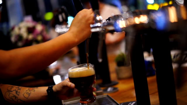 Close-up. Hands of Bartender pouring beer from beer tap in Party Nightclub Pub - video