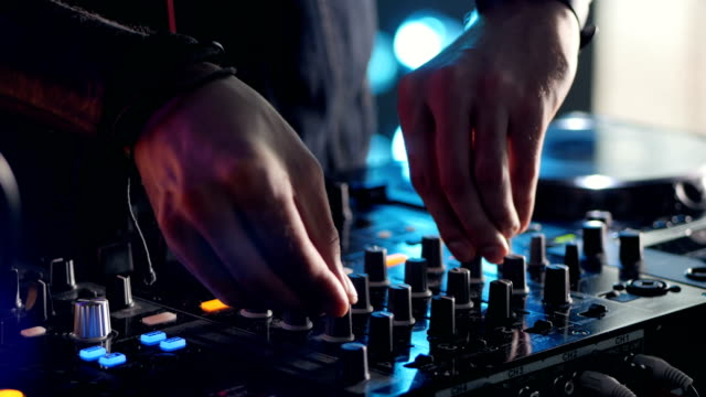 Close-up. Hands of DJ tweak various track controls on DJ mixer console at nightclub party. video