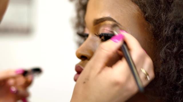 stockvideo's en b-roll-footage met close-up handen van visagist toe te passen en corrigeren van make-up op zwarte afro-amerikaanse model. beauty en fashion concept - oogschaduw
