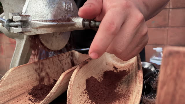 SLO MO Close-up Hands of the barista is grinding coffee beans with an ancient tool in street food