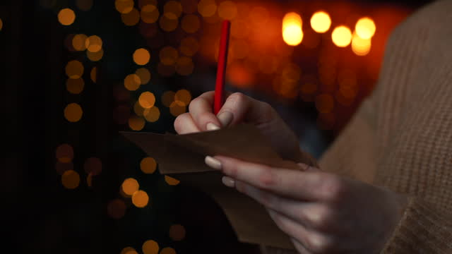 vidéos et rushes de mains de plan rapproché de jeune femme écrivant la lettre de noël au père noël sur l'arbre de noël de fond. - carte postale