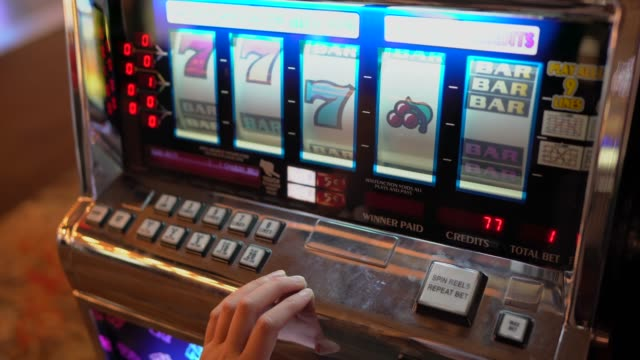 POV closeup hands plays Las Vegas gambling slot machine