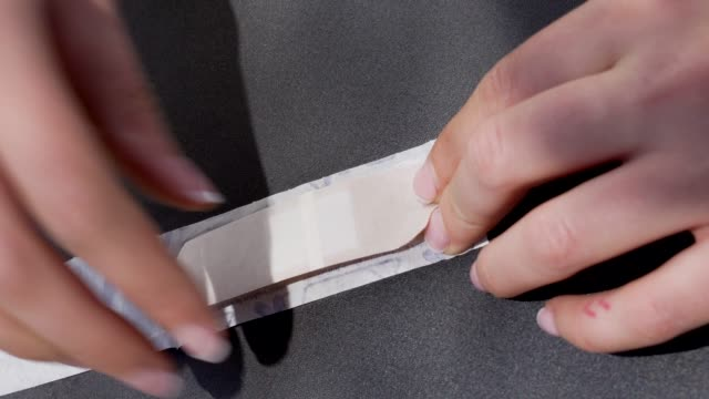 closeup hands removing band aid from packaging video