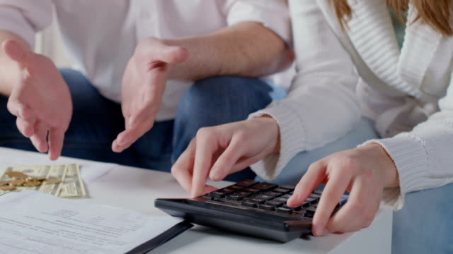 Closeup hands with calculator, husband wife plan family budget