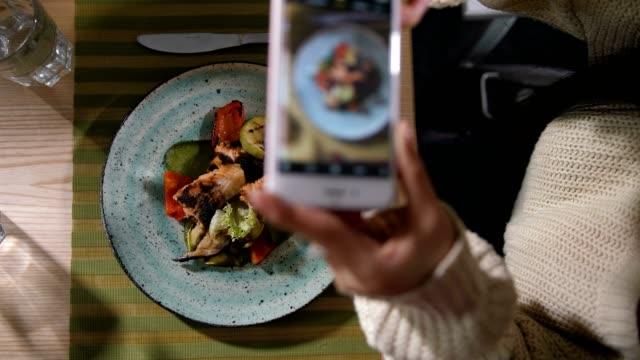 mani ravvicinate con cellulare che scatta foto del pasto - fotografia immagine video stock e b–roll