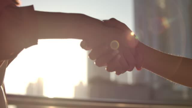 slo mo close-up handshake mit sonnenlicht in der stadt - abmachung stock-videos und b-roll-filmmaterial