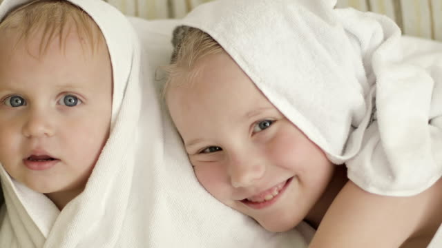 Close-up happy little children after a shower. Close-up happy little children after a shower. A cute boy and girl are sitting in a towel. sister stock videos & royalty-free footage