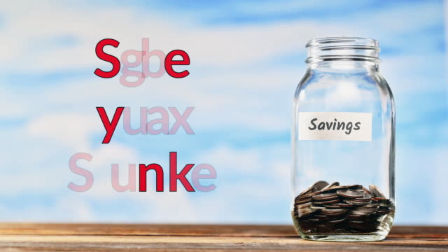 Closeup HD conceptual video of coins falling into a jar with a savings label on the bottle