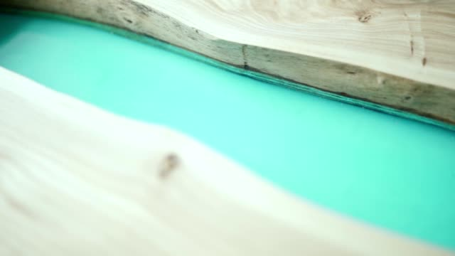 Close-up high angle tracking shot of unfinished tabletop made of wood and turquoise epoxy resin