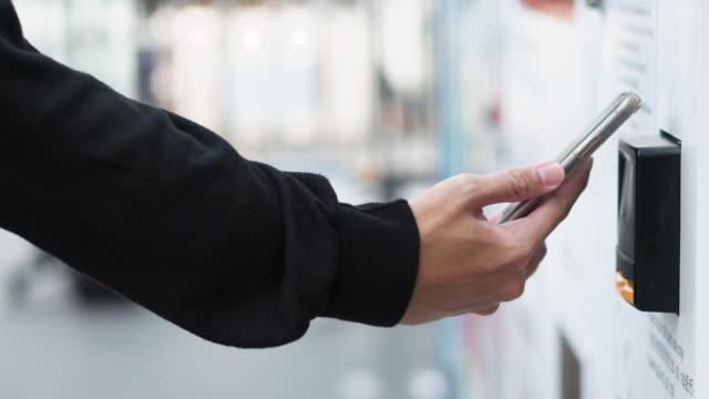 closeup human hand use mobile payment vending machine