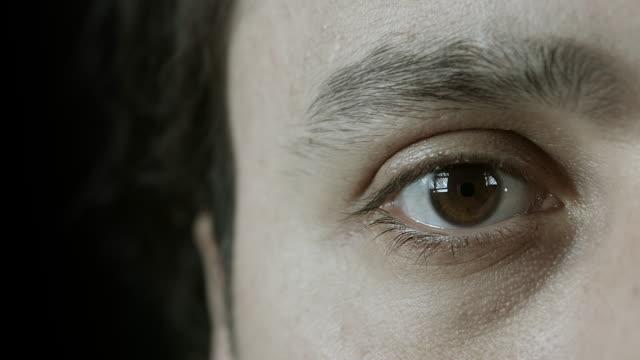 primo piano dell'occhio di uomo - battere le palpebre video stock e b–roll