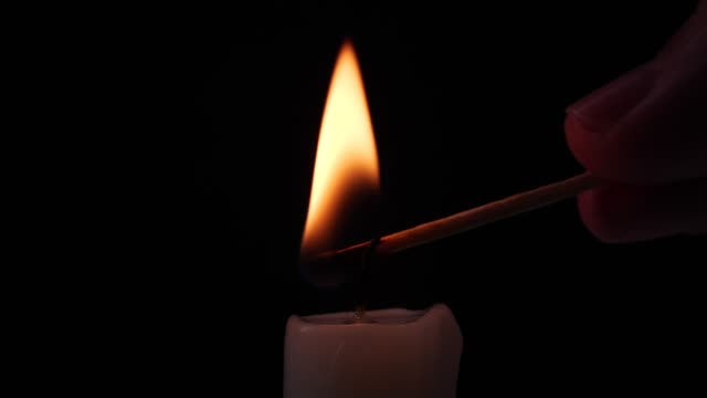 Close-up igniting a candle