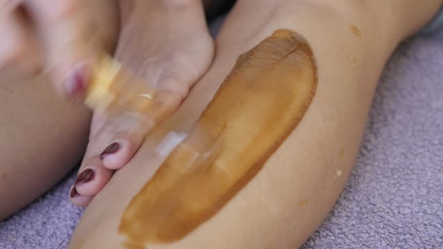 close-up in the studio hair removal with hard warm wax on female body parts 4k 2160p 30fps ultrahd footage - woman health care leg depilation done by professional  3840x2160 uhd video - depilacja filmów i materiałów b-roll