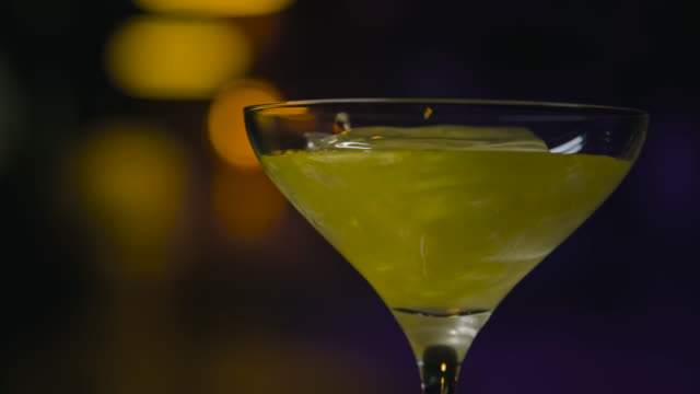 close-up in transparent glass with ice pour shiny drink. stock footage. thick iridescent alcoholic drink is poured into martini glass with ice - martini video stock e b–roll