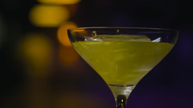 stockvideo's en b-roll-footage met close-up in transparant glas met ijs giet glanzende drank. stockbeelden. dikke iriserende alcoholische drank wordt gegoten in martini glas met ijs - martini