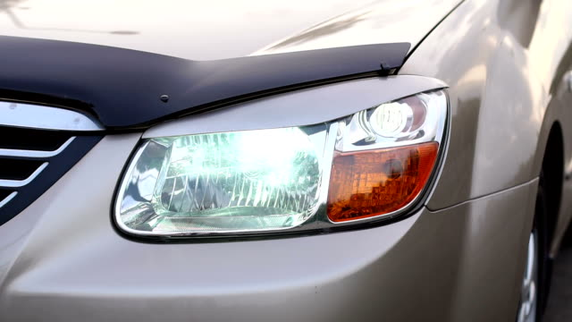 close-up included on headlights on a car at night in the evening. - telecomando background video stock e b–roll