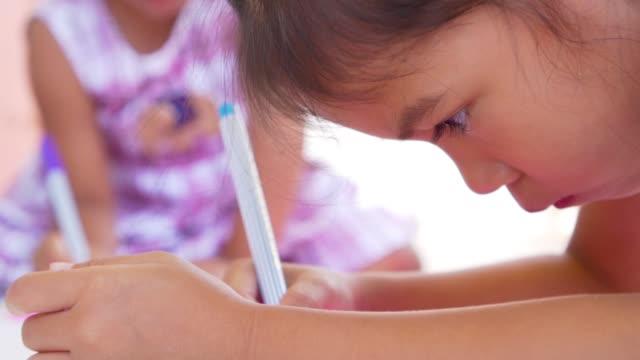 faccia da bambino ravvicinata e usando le penne in feltro colorate su carta, scatto al rallentatore a 50 fps - matita colorata video stock e b–roll