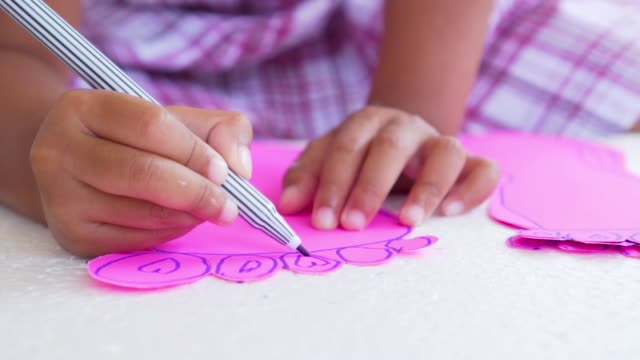Close-up kid hands using the colored felt pens on paper, slow motion shot in 50 fps video