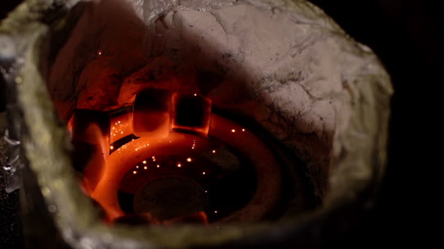 Close-up kindling of square coal for a hookah with a hot spiral in slow motion