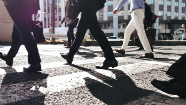 close-up led of business person walking on pedestrian crossing of the road, commuting in big city with crowd of people on the crosswalk - biznes finanse i przemysł filmów i materiałów b-roll