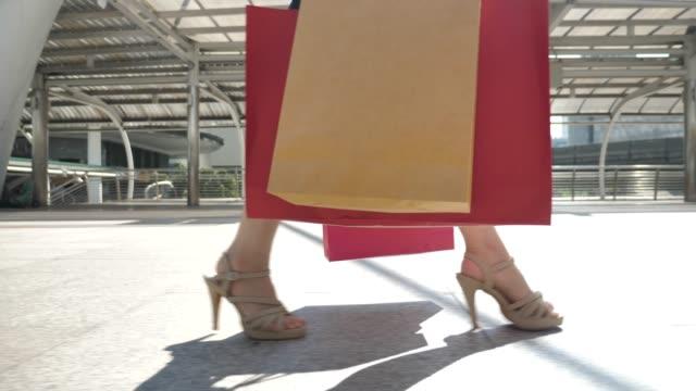 närbild ben gå med kassar efter shoppingdag - köpnarkoman bildbanksvideor och videomaterial från bakom kulisserna