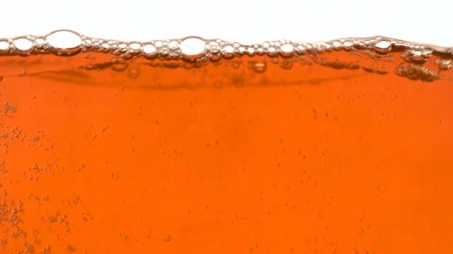 vídeos de stock, filmes e b-roll de close-up líquido de chá. fundo de água abstrata - tea drinks