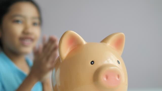 vidéos et rushes de plan rapproché petite fille asiatique mettant la pièce de monnaie dans la métaphore de tirelire économisant l'argent pour un meilleur futur choisissent la profondeur peu profonde de champ - tirelire