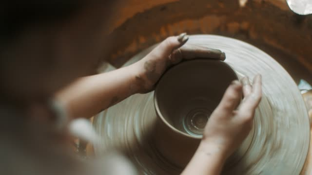 Close-up, little girl using pottery wheel at atelier