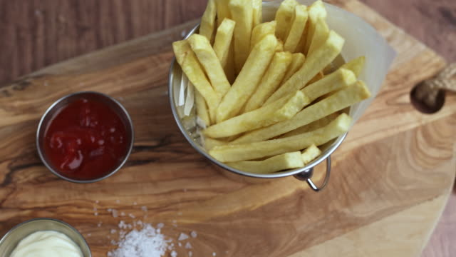 A close-up look of a wooden board with a Bucket full of freshly made French Fries, Mini Serving Buckets with ketchup and mayo along with a pile of sea salt with more chips on the table.
