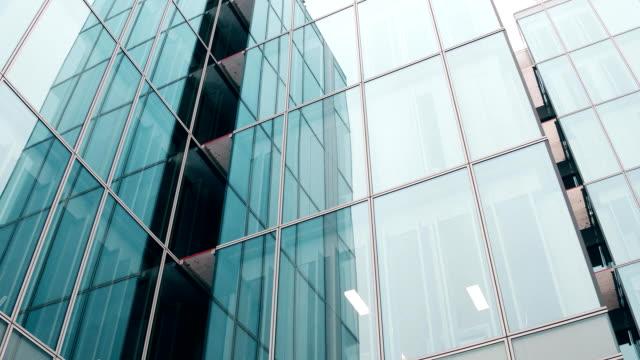 パリの近代的なガラスファサードオフィスビルのクローズアップローアングルステディカムショット。フルhdビデオ - スタビライザー使用点の映像素材/bロール
