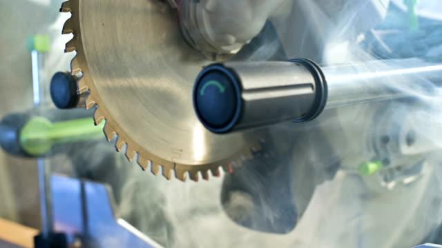 nahaufnahme maschine kreissäge in holz in rauch. - kreissäge stock-videos und b-roll-filmmaterial