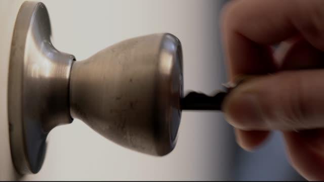 closeup macro hand unlocking a door with a key and opening door video
