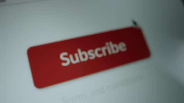 """vídeos de stock, filmes e b-roll de close-up macro shot: tela do dispositivo com site mostrando botão vermelho """"assinar"""", cliques cursor no botão. mock-up concept of digital service subscription: streaming, application, newsletter, software - log on"""