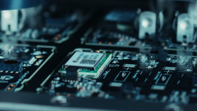 close-up macro shot of electronic factory machine at work: printed circuit board (pcb) being assembled with automated robotic arm, surface mounted technology (smt) connecting microchips to motherboard. - przemysł elektroniczny filmów i materiałów b-roll