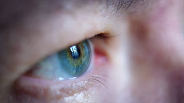 Close-up macro shot of middle age male human blue eye blinking in slow motion.