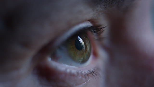 Close-up macro shot of middle age male human brown eye blinking in slow motion.