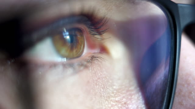 Close-up macro shot of young female human brown eye with vision glasses blinking in slow motion.