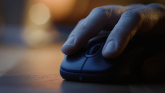 nahaufnahme makro-aufnahme: person es hand mit wireless computer mouse, scrollt durch apps und websites mit einem rad und klicks auf tasten. im hintergrund abendlicht - computermaus stock-videos und b-roll-filmmaterial