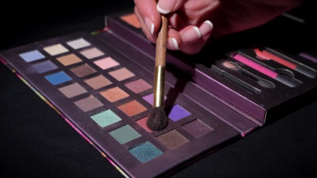 closeup makeup brush on makeup palette This closeup video shows an anonymous hand putting a makeup brush into colorful eyeshadow on a makeup palette with a black background. vanity stock videos & royalty-free footage