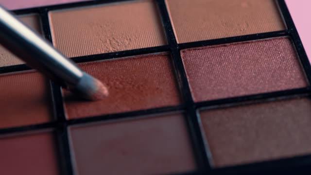 美容院でのブラシ付きクローズアップメイクアップ多色アイシャドウパレット。 - アイシャドウ点の映像素材/bロール