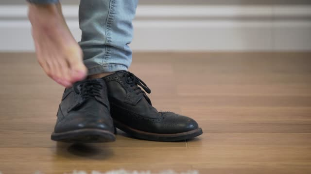 Close-up, male Caucasian feet coming into shot, unrecognizable person taking off broggi boots and leaving. Lifestyle, fashion, footwear.