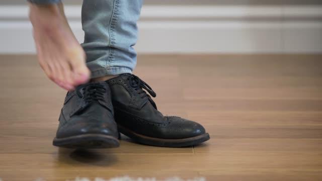 クローズアップ、男性の白人男性の足がショットに入ってきて、認識できない人がブロッジブーツを脱いで去ります。ライフスタイル、ファッション、履物。 - 靴点の映像素材/bロール