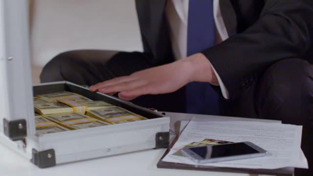 крупным планом мужской руки откройте портфель с пакетами долларов деньги, воспользуйтесь - dollar bill стоковые видео и кадры b-roll