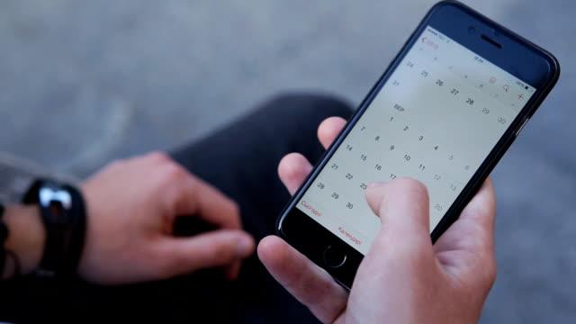 vídeos de stock, filmes e b-roll de close-up de mãos de homens rolagem tela do smartphone. pessoa usando o aplicativo de calendário no dispositivo móvel. - calendário
