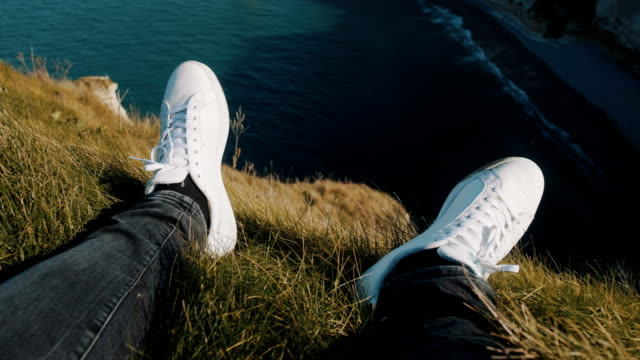 Close-up male legs in white sneakers on rock edge, tiltup watching epic white sea cliffs at wonderful Etretat France.